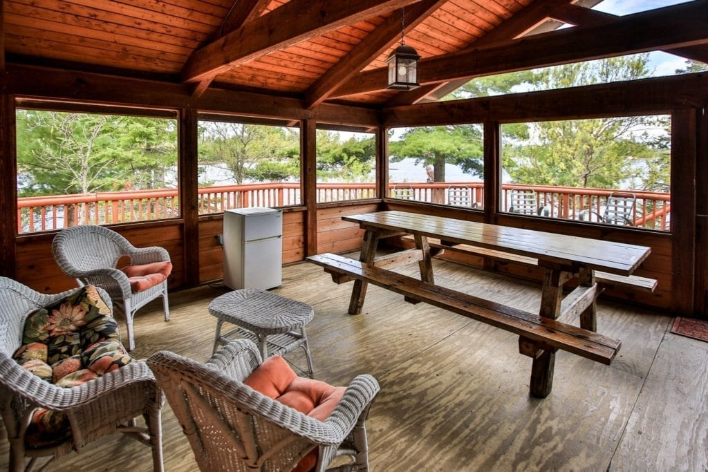 Firestone Log Lodge enclosed patio with picnic table and rattan chairs.