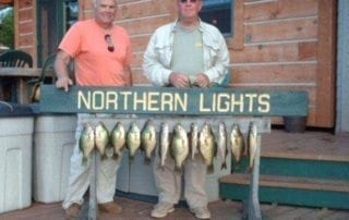 Two men standing with several caught bass.