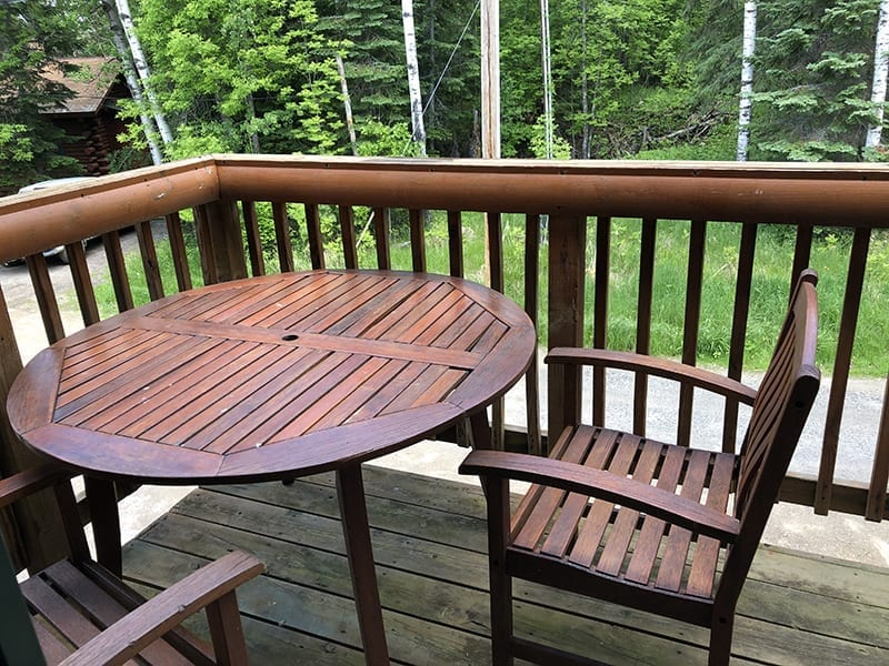 Treehouse cabin patio deck with wooden table and chairs.
